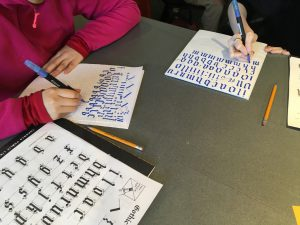 Hands of children doing Gothic calligraphy