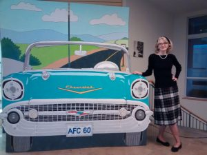 A picture of Michele Nidenoff, illustrator, wearing 1950s garb, standing beside a cut-out mural of a 1959 Chevy Belaire.