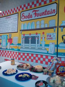 A painting of a 1950s soda fountain.
